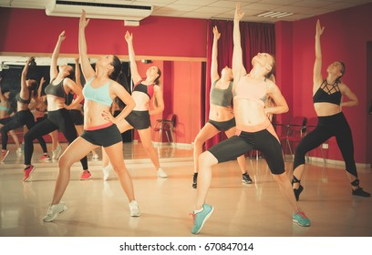 Group of young slim athletic women exercising dance training in class