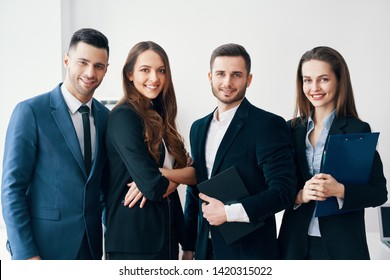 Group of young and smiling business people in modern office. Success teamwork concept