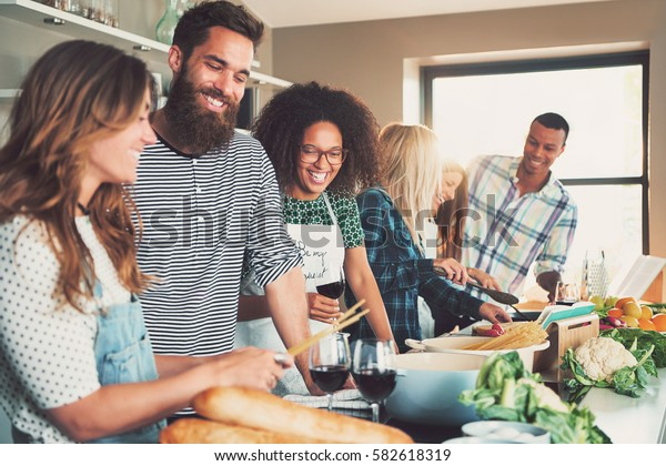 Group of young smiling cheerful friends cooking some meal at kitchen with wine glasses, they drink simultaneously.