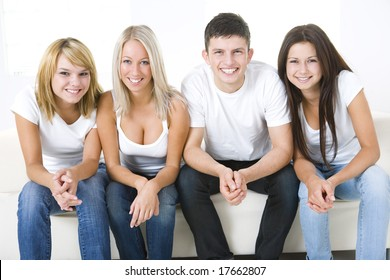 Group of young smiling friends sitting on a couch and looking at camera. Front view.