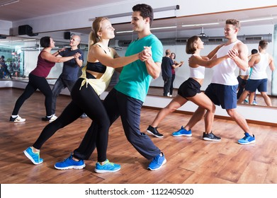 Group of young smiling people learning salsa at dance class. Focus on brunet man