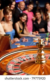 group of young smiling people looking excited at spinning roulette