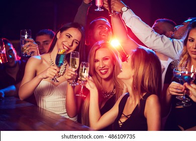 Group of young smiling people sitting at the bar and  toasting with wine, beer and cocktails
