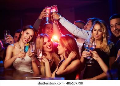 Grupo de jovens sorrindo sentados no bar e brindando com vinho, cerveja e coquetéis