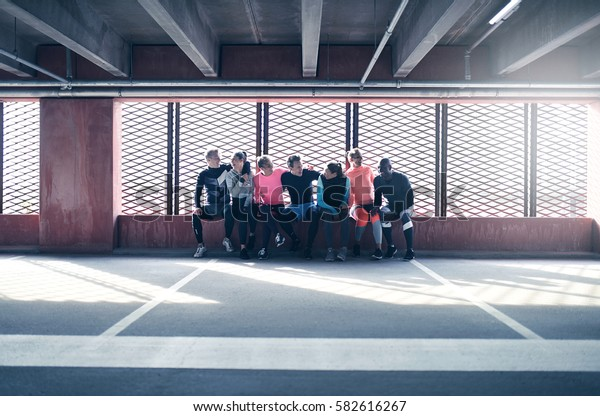 Group of young sportive adults in sportswear sitting together and laughing at athletic field against barred window.