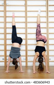 Group of young sports woman does an extension exercise at the Swedish wall