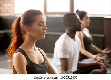 Group of young sporty afro american and caucasian people practicing yoga lesson, sitting in Sukhasana exercise, Easy Seat pose, working out, students training in sport club, studio close up