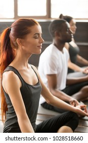 Group of young sporty afro american and caucasian people practicing yoga lesson, sitting in Easy Seat exercise, Sukhasana pose, working out, students training in sport club, studio close up