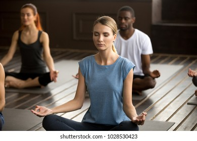 Group of young sporty afro american and caucasian people practicing yoga lesson, sitting in Sukhasana exercise, Easy Seat pose with mudra gesture, working out, students training in club, studio