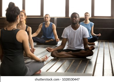 Group of young sporty afro american and caucasian people practicing yoga lesson with instructor, sitting in Sukhasana exercise, Easy Seat pose, working out, students training in sport club, studio
