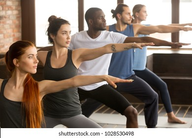 Group of young sporty afro american and caucasian people practicing yoga lesson, standing in Warrior two exercise, Virabhadrasana II pose, working out, indoor close up, studio background