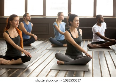 Group of young sporty afro american and caucasian people sitting in Parivritta Sukhasana exercise, students working out in club, indoor, studio