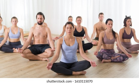 Group of young sporty attractive people in yoga studio, practicing yoga lesson with instructor, sitting on floor in Siddhasana, easy seated yoga pose. Healthy active lifestyle, working out in gym.