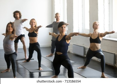 Group of young sporty attractive people practicing yoga lesson with instructor, standing in Warrior Two exercise, Virabhadrasana pose, working out, indoor, studio. Wellbeing, wellness concept