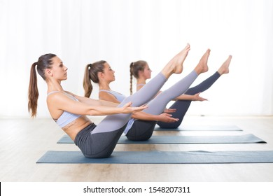 Group of young sporty attractive women in yoga studio, practicing yoga lesson with instructor, forming a line in Navasana, boat asana yoga pose. Healthy active lifestyle, working out indoors in gym.