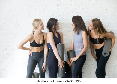 Group of young sporty girls with fitness mats talking. Chatting while having a break, exchanging news, sharing diet and exercise tips, making true friends in yoga community, studio