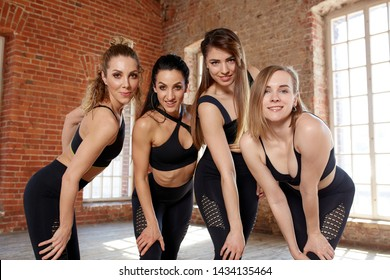 A group of young sporty girls standing in the hall for dancing. Female companions in the gym, relaxing after fitness, indoors to their full height, loft studio, copy space