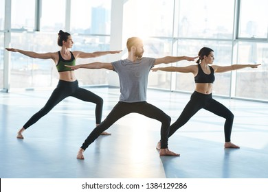 Group of young sporty people in activewear standingon the floor in one of yoga positions with their arms outstretched