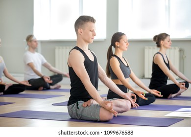 Group of young sporty people doing yoga in gym, Sukhasana exercise, Easy Seat pose, working out, indoor full length, students training in sport club, studio. Mindfulness, wellness, wellbeing concept