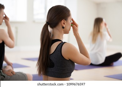 Group of young sporty people doing yoga, Alternate Nostril Breathing exercise, nadi shodhana pranayama, indoor close up, students working out in sport club, rear view. Wellness, wellbeing concept