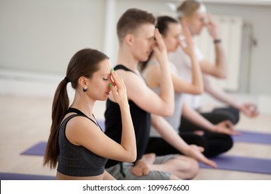 Group of young sporty people doing yoga, Alternate Nostril Breathing exercise, nadi shodhana pranayama, working out indoor close up, students training in sport club studio. Wellness, wellbeing concept