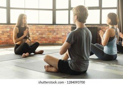 Group of young sporty people doing yoga with teacher, sitting in Sukhasana exercise, Easy Seat pose, practice of meditation concept