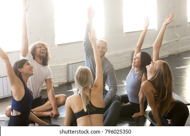 Group of young sporty people joining raised arms. Team building exercise, excited students satisfied after productive workout, sitting in a circle on the floor, express common choice or opinion