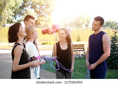 Group of young sporty people with jumping ropes outdoors