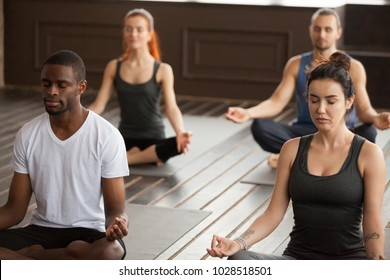 Group of young sporty people practicing yoga lesson, meditating sitting in Sukhasana exercise, Easy Seat pose, hand mudra gesture, working out, students training in club, indoor close up, studio