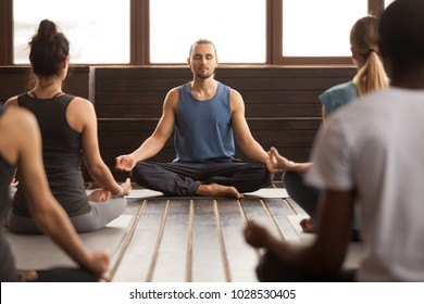 Group of young sporty people practicing yoga lesson with male instructor, sitting in Sukhasana exercise, Easy Seat pose, working out, students training in sport club, studio