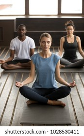 Group of young sporty people practicing yoga lesson with instructor, sitting in Sukhasana exercise with eyes closed, Easy Seat pose, mudra gesture, students working out in club, indoor, studio