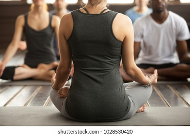 Group of young sporty people practicing yoga lesson with instructor, sitting in Sukhasana exercise, Easy Seat pose, working out, students training in sport club, studio, trainer rear view, close up
