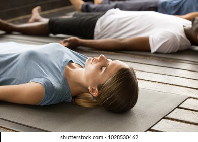 Group of young sporty people practicing yoga lesson lying in Dead Body or Corpse pose, Savasana exercise, working out, resting after practice, indoor close up, studio. Healthy lifestyle concept