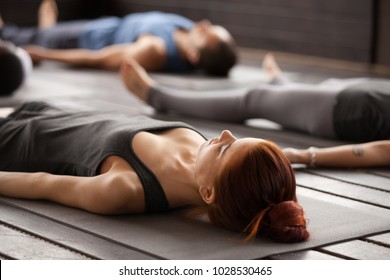 Group of young sporty people practicing yoga lesson lying in Dead Body or Corpse pose, Savasana exercise, working out, resting after practice, indoor close up, studio