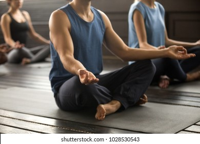Group of young sporty people practicing yoga lesson, sitting in Sukhasana exercise, Easy Seat pose, mudra gesture, students working out in club, indoor, studio close up