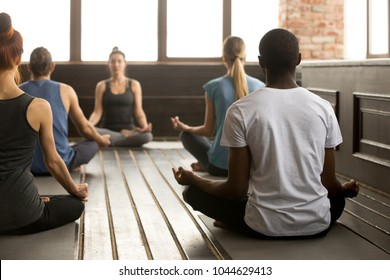 Group of young sporty people practicing yoga lesson with instructor, sitting in Sukhasana exercise, Easy Seat pose, working out, training in sport club, studio, students rear view