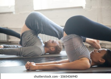 Group of young sporty people practicing yoga lesson, doing Halasana exercise, Plough pose, working out, indoor close up view, students training in club, studio. Healthy lifestyle concept