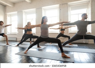 Group of young sporty people practicing yoga lesson, doing Warrior Two exercise, Virabhadrasana 2 pose, working out, indoor full length, students training in sport club, studio