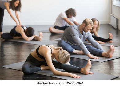 Group of young sporty people practicing yoga lesson with instructor, doing Janu Sirsasana pose, Head to Knee Forward Bend exercise, working out, in yoga studio