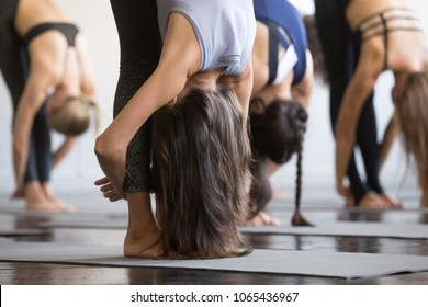 Group of young sporty people practicing yoga lesson, standing forward bend, head to knees exercise, uttanasana pose, working out, indoor close up view photo, studio