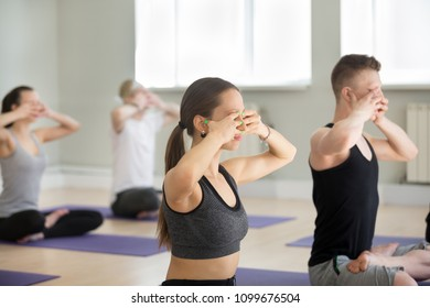 Group of young sporty people practicing yoga lesson, doing Bhramari Pranayama exercise, Humming Bee Breathing, Sukhasana pose, working out, indoor full length, students training in sport club, studio