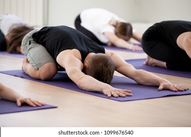 Group of young sporty people practicing yoga lesson, doing Child exercise, resting in Balasana pose, working out, indoor studio session close up, students training in club. Healthy wellbeing lifestyle