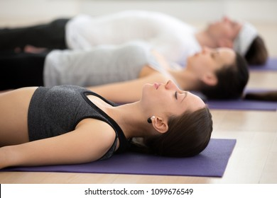 Group of young sporty people practicing yoga lesson, doing Savasana pose, Corpse exercise, Dead Body, indoor close up, students working out in sport club, studio. Wellness, wellbeing concept