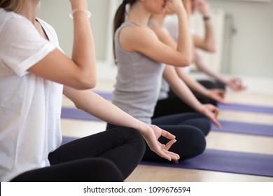 Group of young sporty people practicing yoga lesson in gym, doing Alternate Nostril Breathing exercise, nadi shodhana pranayama pose, working out, indoor close up, students training in sport club