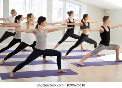 Group of young sporty people practicing yoga, doing Warrior II exercise, Virabhadrasana 2 pose, indoor full length, yogi students working out in sport club, studio. Active lifestyle, wellness concept