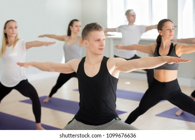 Group of young sporty people practicing yoga lesson, doing Warrior exercise, Virabhadrasana 2 pose, working out, indoor close up, yogi students training in sport club, studio. Active lifestyle concept
