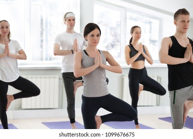 Group of young sporty people practicing yoga lesson, doing Vrksasana exercise, Tree pose, working out, indoor full length, students training in sport club. Wellness, healthy lifestyle concept
