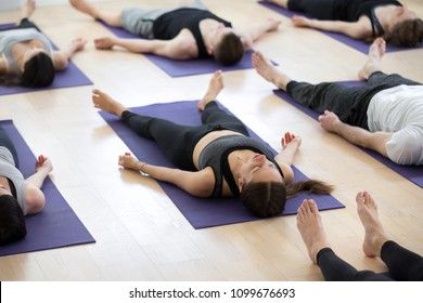 Group of young sporty people practicing yoga lesson, doing Savasana pose, Corpse exercise, Dead Body, working out, indoor full length, students training in sport club, studio