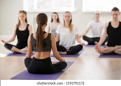 Group of young sporty people practicing yoga with instructor, doing Sukhasana exercise, Easy Seat pose, working out, students training in club, studio close up, teacher back view. Well-being concept