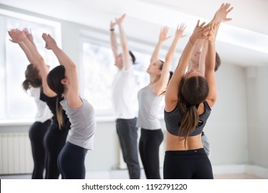 Group of young sporty people practicing yoga lesson, doing Tadasana exercise, mountain pose, working out, indoor full length, yogi students training in sport studio club. Well-being concept
